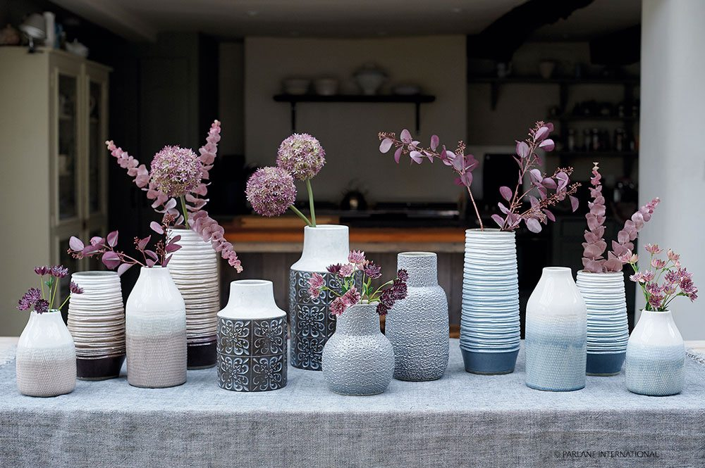 Composition of white and blue vases with purple flowers