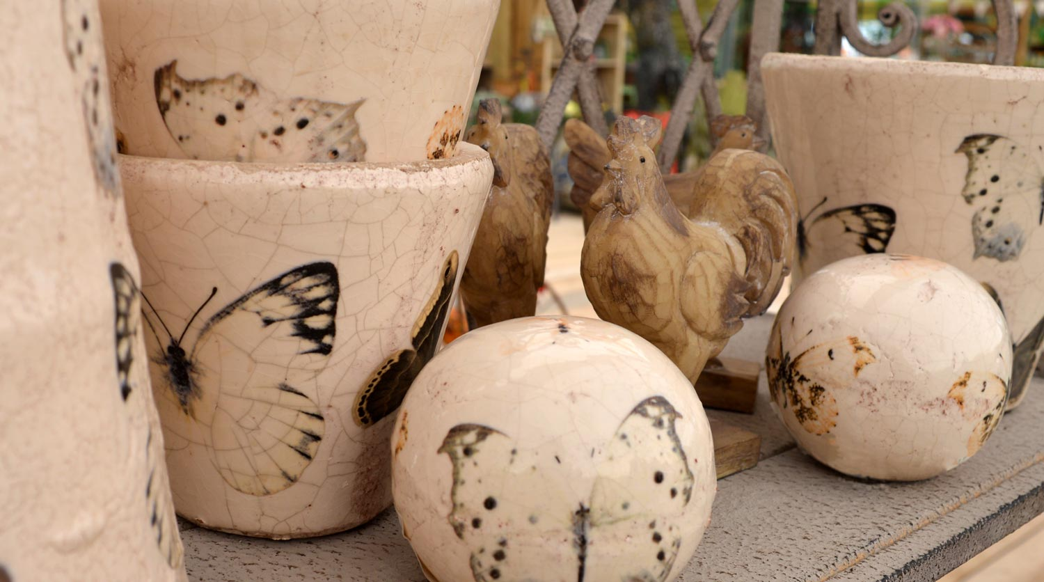 Cracked-effect ceramic pots and balls with butterfly print. Wooden chickens in background
