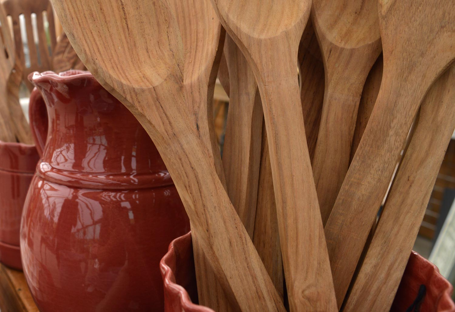 Wooden spoons in a red vase